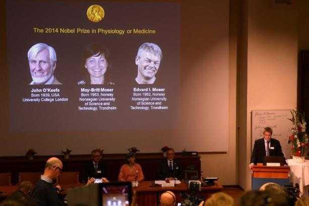 Una pantalla muestra unas imágenes de los investigadores John O'Keefe y May-Britt y Edvard I. Moser, distinguidos con el premio Nobel de Medicina el 6 de octubre de 2014 en Estocolmo