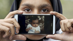Migrant Rubina from Kabul, Afghanistan, shows a picture of her nephew Iman as she waits to cross the Slovenia-Austria border in Sentilj, Slovenia October 27, 2015. REUTERS/Srdjan Zivulovic
