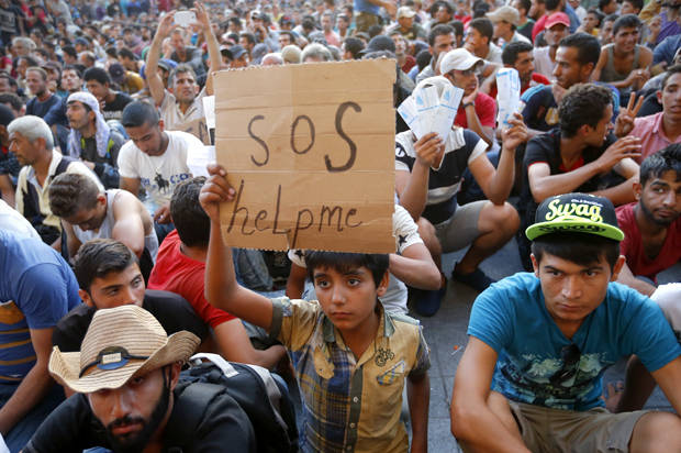 "A child holds a self-made placard reading ""SOS help me"" outside the railways station in Budapest, Hungary September 2, 2015. Hundreds of migrants protest in front of Budapest's Keleti Railway Terminus for a second straight day on Wednesday, shouting ""Freedom, freedom!"" and demanding to be let onto trains bound for Germany from a station that has been closed to them by Hungarian riot police officers.  REUTERS/Laszlo Balogh         - RTX1QSCX"