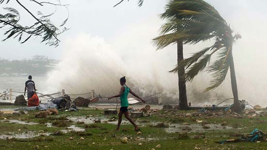 REFILE - CLARIFYING DISCLAIMER  Local residents walk past debris as a wave breaks nearby in Port Vila, the capital city of the Pacific island nation of Vanuatu March 14, 2015. Winds of up to 250 kilometers an hour (155 mph) ripped metal roofs off houses and downed trees in Vanuatu on Saturday, as relief agencies braced for a major rescue operation and unconfirmed reports said dozens had already died. Witnesses described sea surges of up to eight meters (yards) and flooding throughout the capital Port Vila after the category 5 cyclone named Pam hit the country late on Friday.   REUTERS/UNICEF Pacific/Handout via Reuters   (VANUATU - Tags: DISASTER ENVIRONMENT) ATTENTION EDITORS - THIS PICTURE WAS PROVIDED BY A THIRD PARTY. REUTERS IS UNABLE TO INDEPENDENTLY VERIFY THE AUTHENTICITY, CONTENT, LOCATION OR DATE OF THIS IMAGE. FOR EDITORIAL USE ONLY. NOT FOR SALE FOR MARKETING OR ADVERTISING CAMPAIGNS. NO SALES. NO ARCHIVES. THIS IMAGE WAS PROCESSED BY REUTERS TO ENHANCE QUALITY, AN UNPROCESSED VERSION WILL BE PR