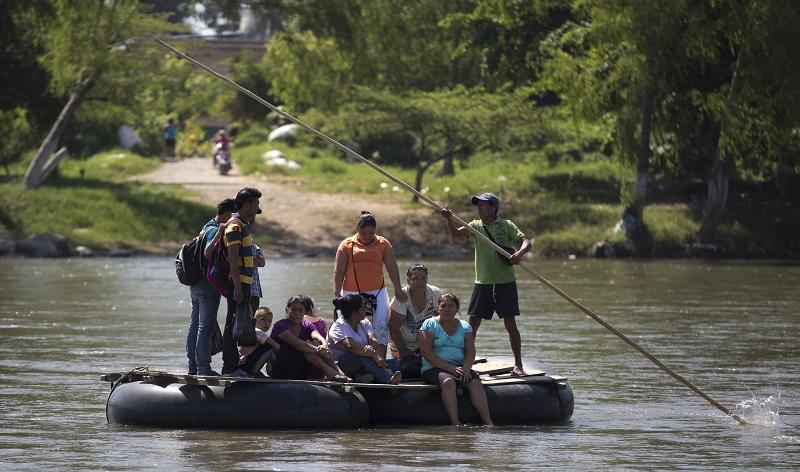 Imagen del 11 de julio 2014 de varios inmigrantes en la frontera de Mexico, cruzando el río Suchiate en una barca improvisada.   (AP Photo/Eduardo Verdugo)
