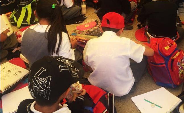 niños toman clases en el piso